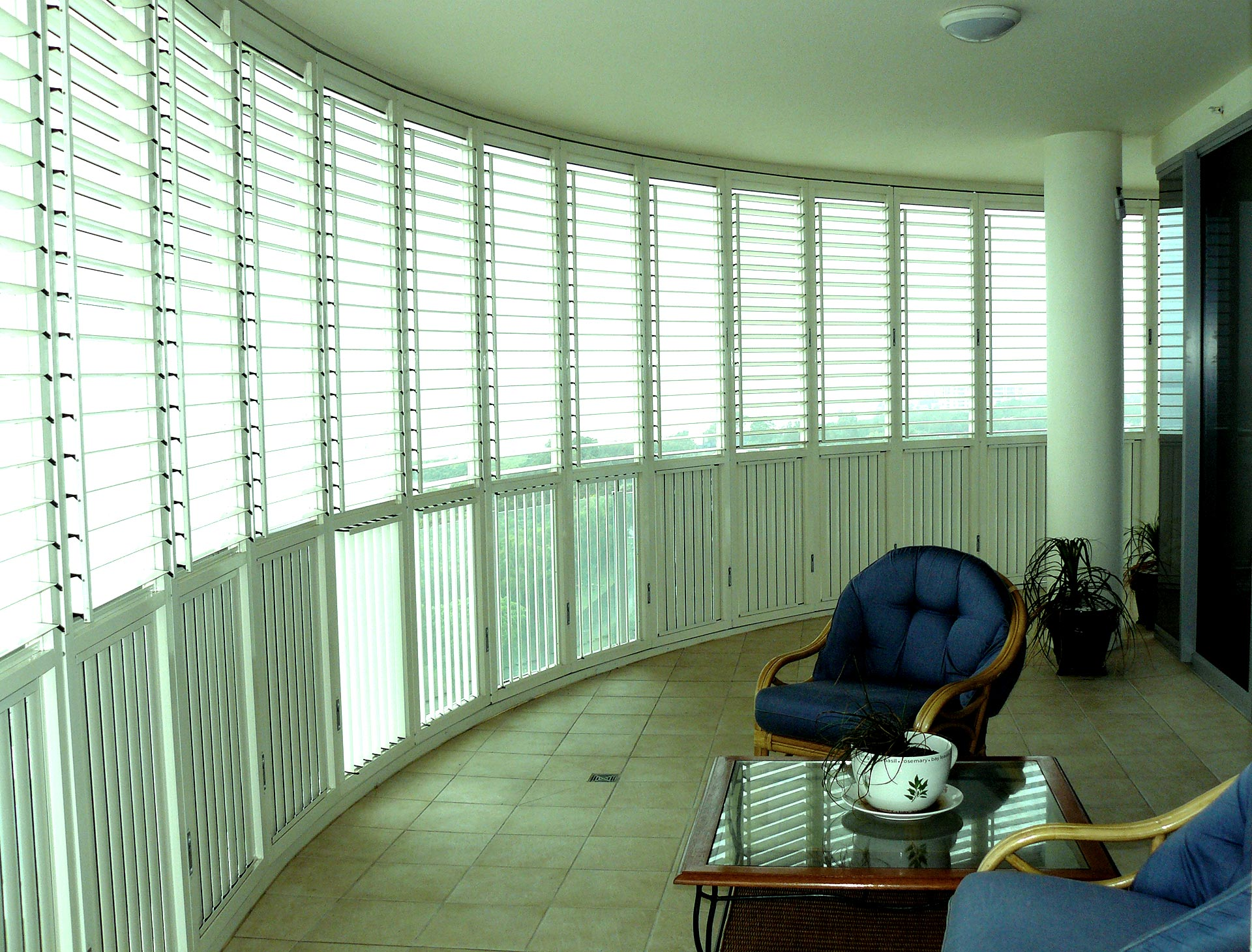 White outdoor shutters creating an outside room across a balcony